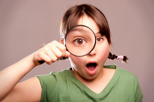 虫眼鏡を通してカメラを見て少女