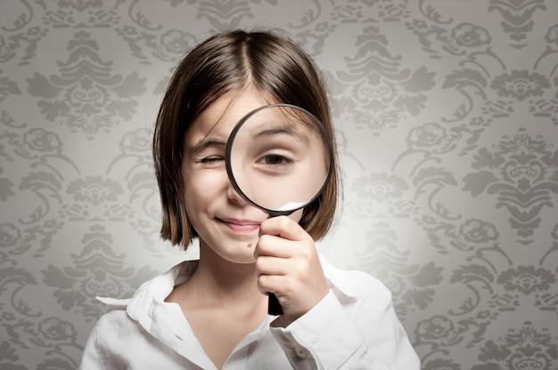 Маленькая девочка смотрит в камеру через увеличительное стекло