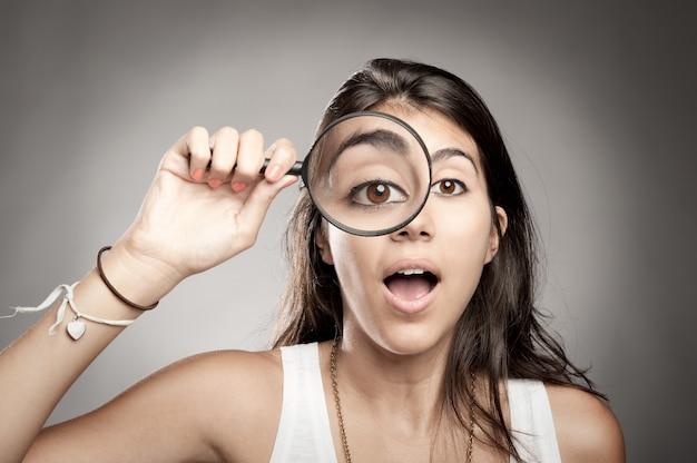虫眼鏡を通してカメラを見ている女性