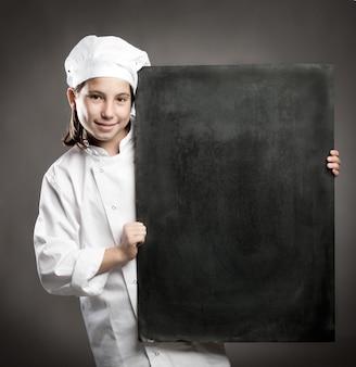 メニューの黒板を保持している若いシェフ