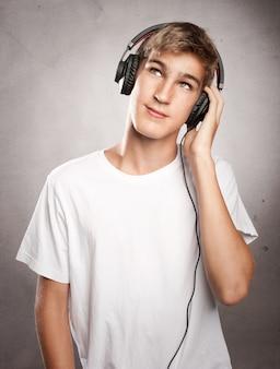 Наушники молодого человека нося слушая к музыке на серой предпосылке