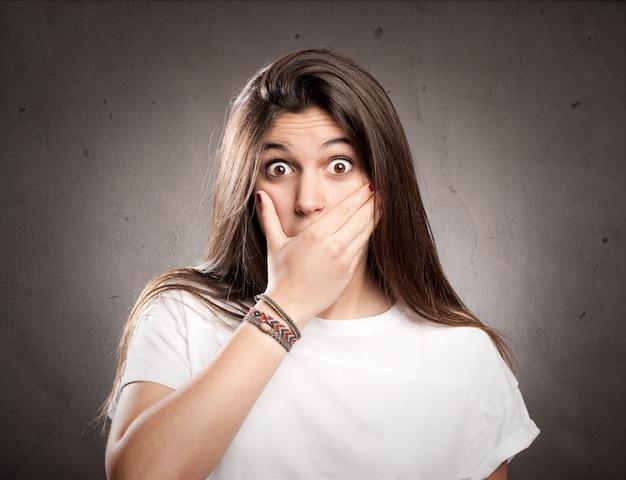 Молодая удивленная девушка закрыла рот рукой