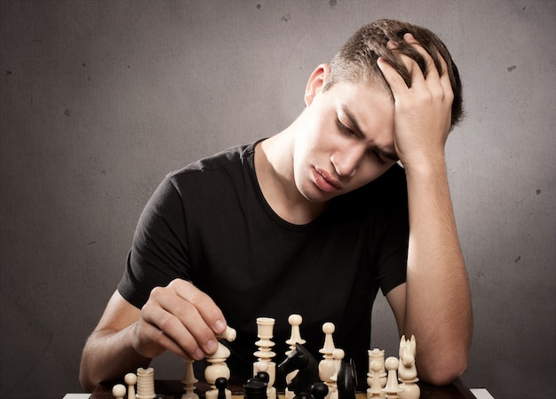 Сосредоточенный молодой человек играет в шахматы