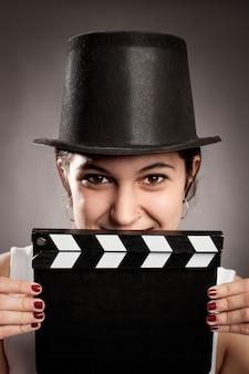 映画クラッパーボードを保持している若い女の子