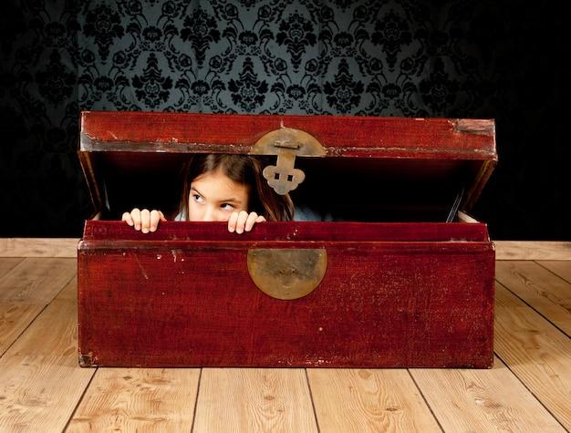 ビンテージ背景を持つ古代のトランクの中の少女