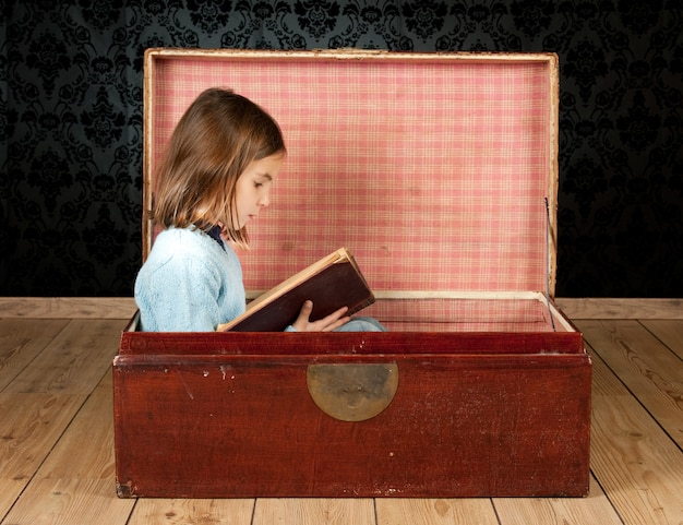 ビンテージ背景の本を読んで古代のトランクの中の少女