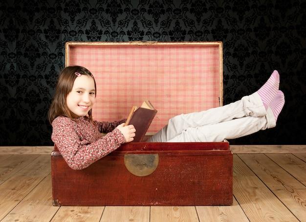 ビンテージ背景で本を読んで古代のトランクの中の少女