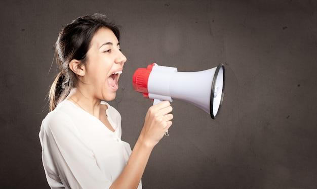 灰色の背景にメガホンで叫んでいる若い女性