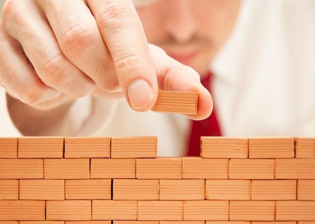 壁を構築するビジネスマン