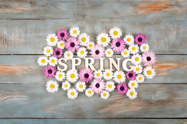 青い木製の背景の花の春の言葉