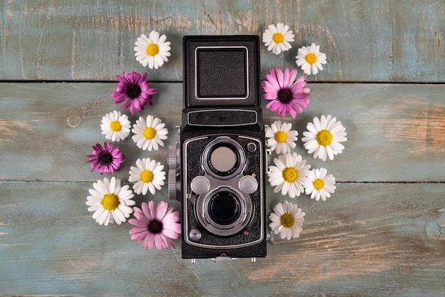 青い木製の背景の花の古いカメラ
