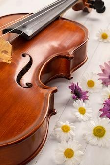 白い木製の背景の花とヴァイオリン