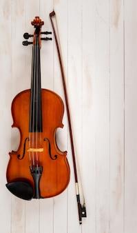 白い木製の背景のバイオリン