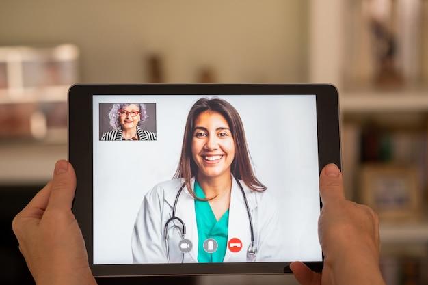 Пожилая женщина, имеющая видео звонок консультации с врачом на планшете