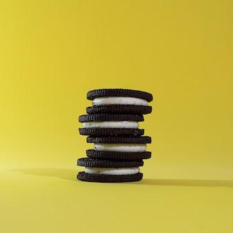 黄色の背景に積み上げられたクリームとチョコレートクッキー。