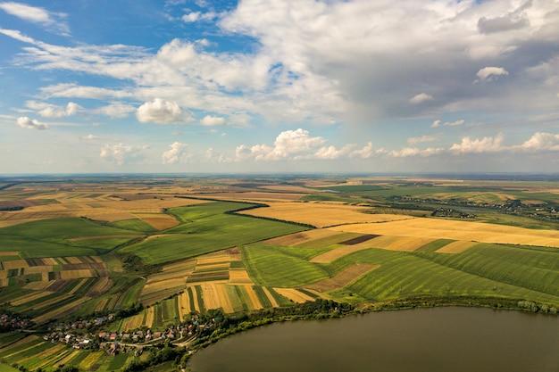 Воздушный сельский ландшафт с желтыми залатанными полями земледелия и голубым небом с белыми облаками.