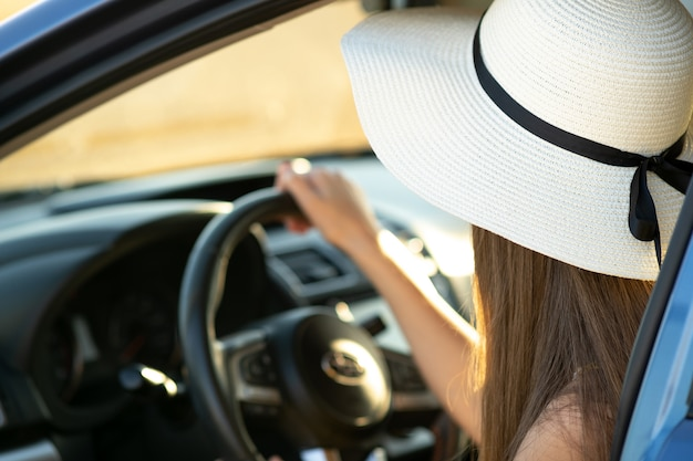 Женщина в желтой соломенной шляпе сидит за рулем