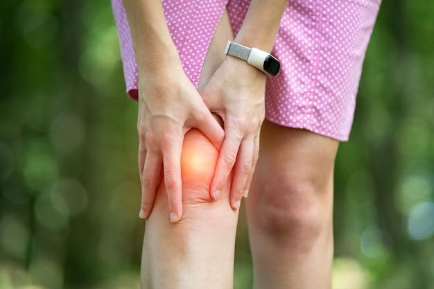 Женщина, держащая ее колено с руками, имеющими боль в суставах