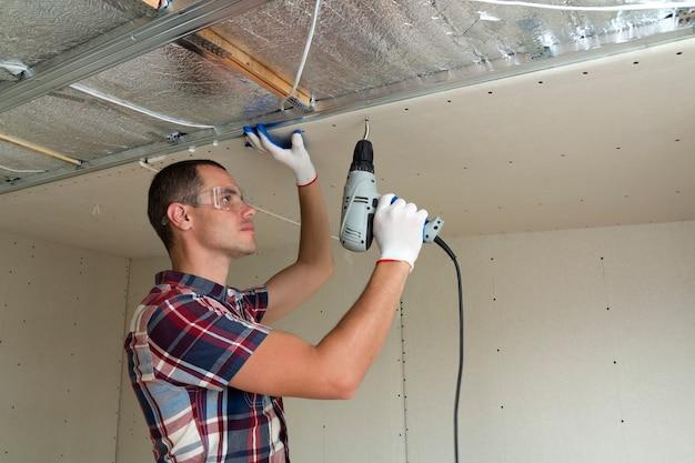 金属フレームに乾式壁吊り天井を固定するゴーグルの若い男