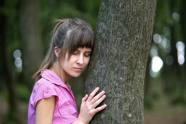 Молодая женщина, опираясь на ствол дерева в лесу летом.