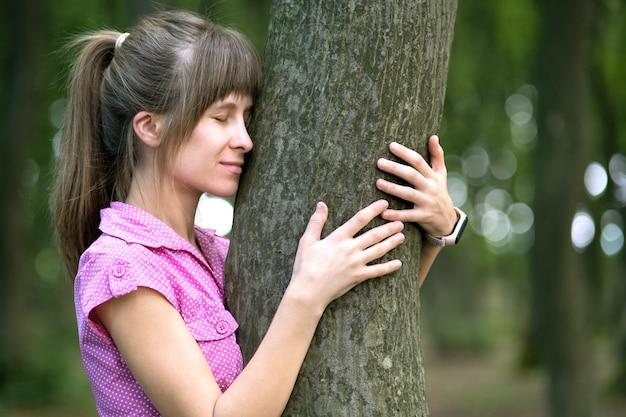 夏の森の木の幹にもたれて若い女性。