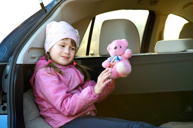 Довольно счастливая детская девочка играет с розовым игрушечным мишкой, сидящим в багажнике автомобиля