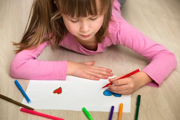 カラフルな鉛筆で描く子供の女の子
