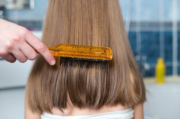 子供の女の子の髪をとかすブラシで母の手。