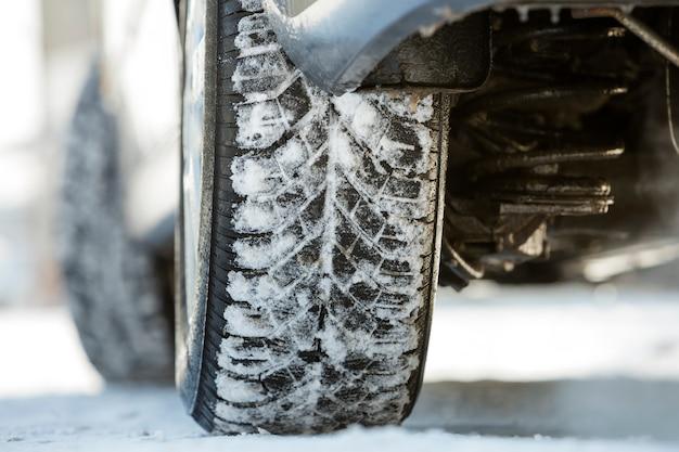 深い雪の中で車の車輪のゴム製タイヤ