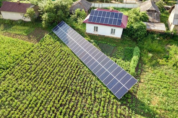 青いソーラーパネルのある家の空撮。