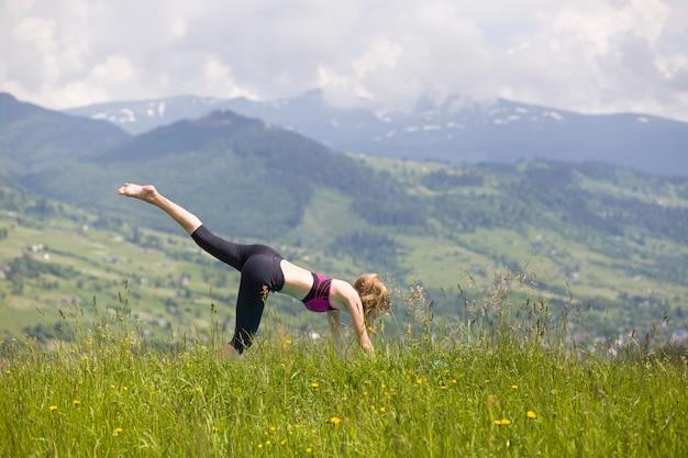 屋外のヨガの練習を行う若い女性