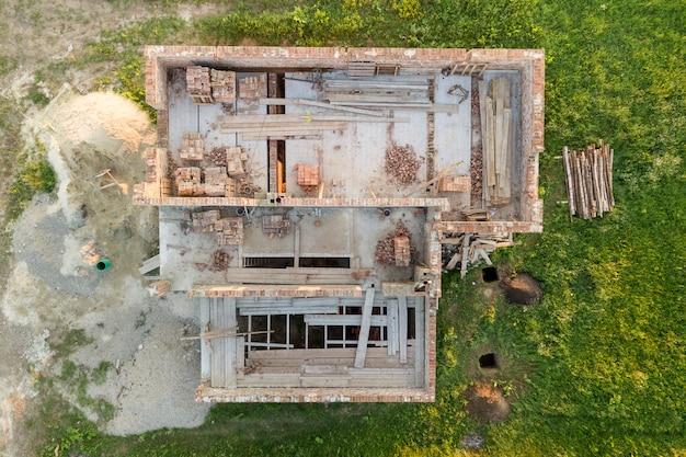 Кирпичный цокольный этаж и штабели кирпича для строительства