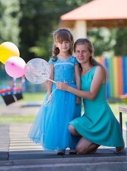 金髪の母と長い青いイブニングドレスの小さな娘の女の子
