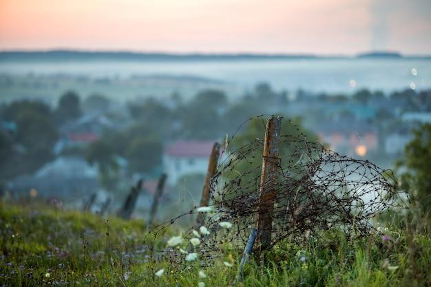 Старая большая колючая проволока наматывается на ржавый столб