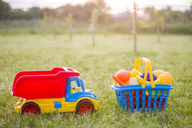 車のトラックとおもちゃの果物と野菜のバスケット。日当たりの良い夏の日に屋外の子供のための明るいプラスチック製のカラフルなおもちゃ。