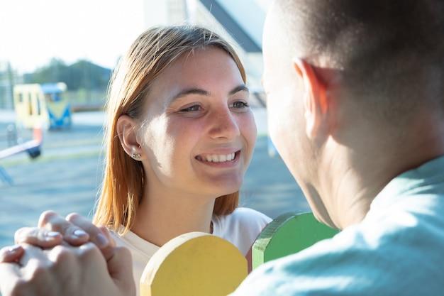 幸せな若いカップルは屋外。女の子と男の子がお互いを見て。