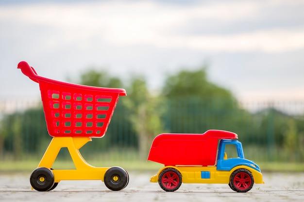 日当たりの良い夏の日に屋外の子供のための明るいプラスチック製のカラフルなおもちゃ。車のトラックとショッピング手押し車。