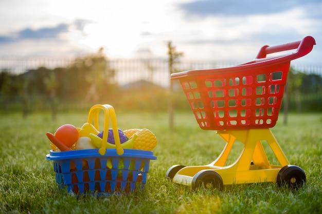 ショッピングの手押し車とおもちゃの果物と野菜のバスケット。日当たりの良い夏の日に屋外の子供のための明るいプラスチック製のカラフルなおもちゃ。