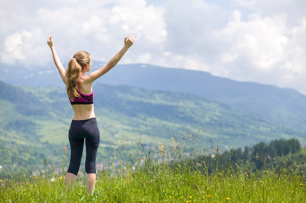 日当たりの良い夏の日の美しい山の風景の背景に屋外に上げられた腕を持つスリムな若い女性。