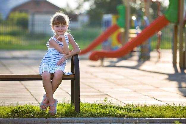 日当たりの良い夏の日に遊び場のベンチに一人で屋外に座って短いドレスでかわいい若い女の子。