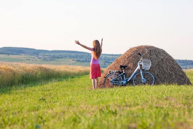 Молодая женщина с велосипедом на поле с стогами сена в солнечный день