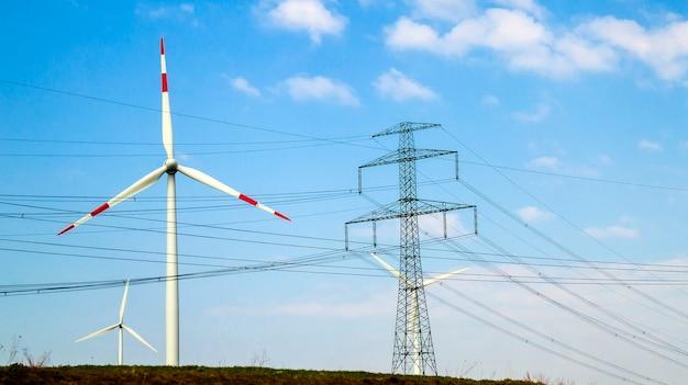 青い空を背景に高電圧塔と風力タービン
