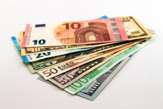 米ドル紙幣と白い背景の上のユーロ紙幣。