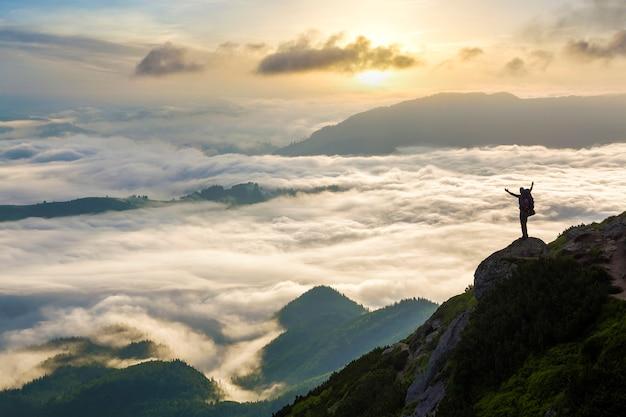 Широкая горная панорама. маленький силуэт туриста с рюкзаком на скалистом склоне горы с поднятыми руками над долиной, покрытой белыми тучными облаками.