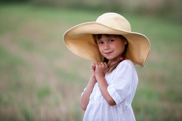 Юная модная милая милая девушка с длинными косами в красивом белом летнем платье и большой соломенной шляпе.