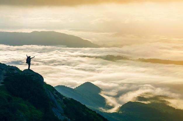 Широкая горная панорама. маленький силуэт туриста с рюкзаком на скалистом склоне горы