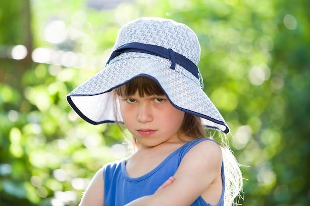 大きな帽子の深刻な少女のクローズアップの肖像画。夏の屋外の時間を楽しんでいる子。