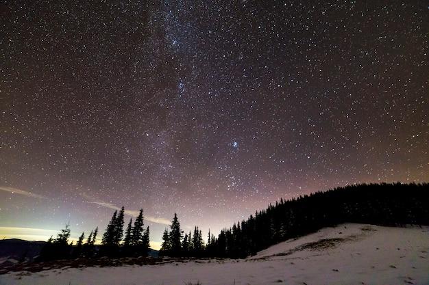 冬の山の夜の風景のパノラマ。暗い青い星空の天の川明るい星座