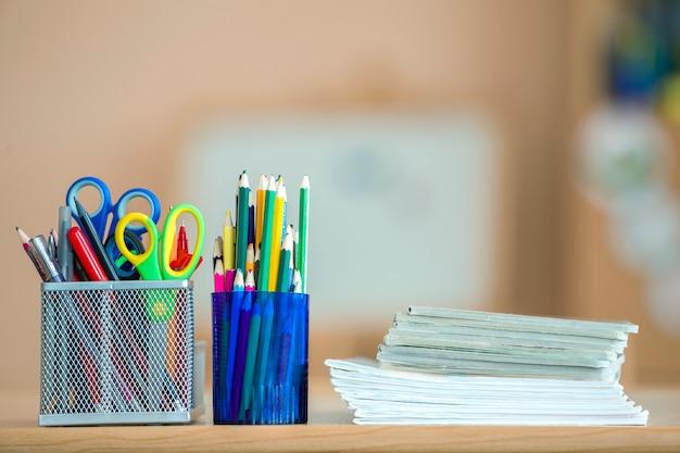 ノートブック、カラフルな描画鉛筆、文房具の配置のスタック