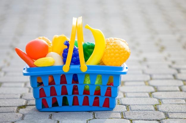 おもちゃの果物と野菜で明るいプラスチック製のカラフルなバスケット